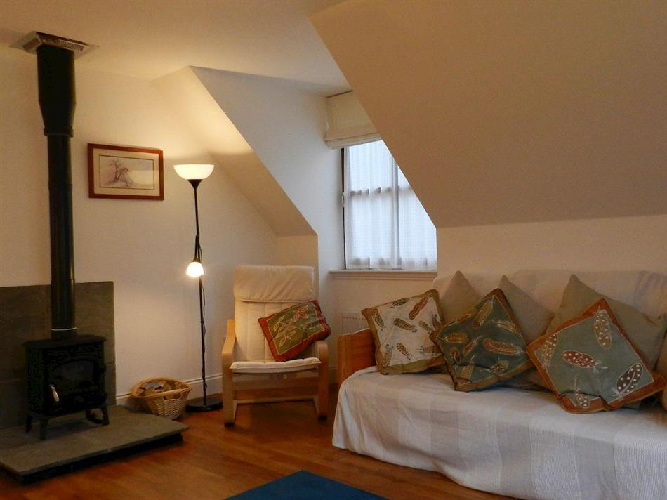 Living room with a wood burner in Seaview Cottage, Lamlash, Isle of Arran