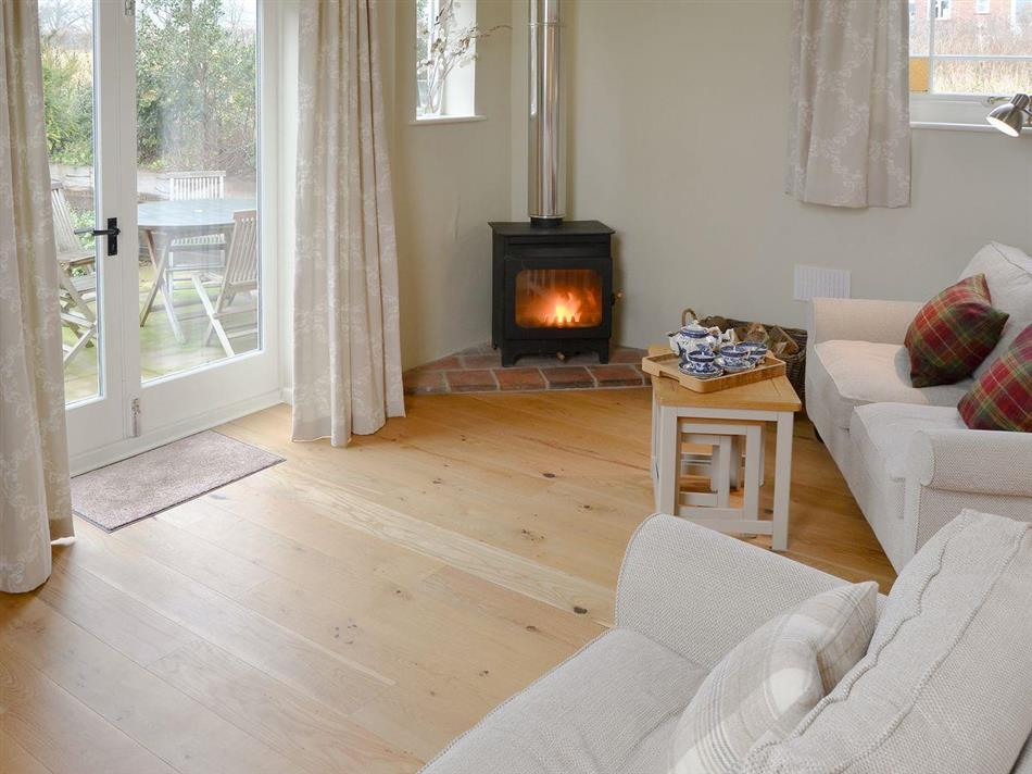 Living room with the wood burner in The Old Chapel, Itteringham, near Aylsham